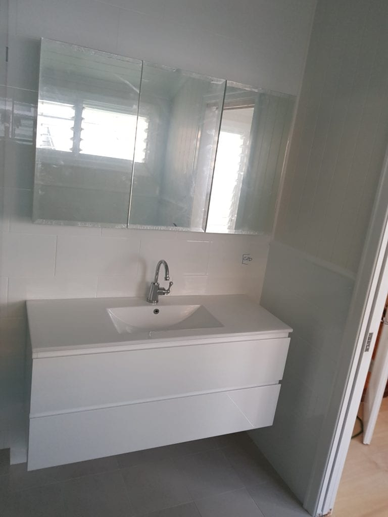 New Vanity with mirror and white tiles in renovated house